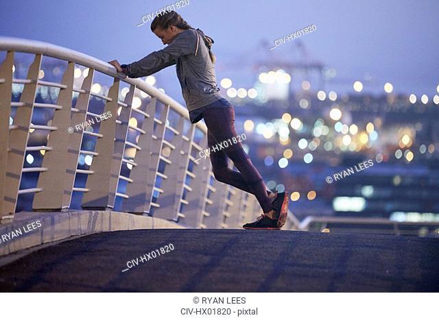 Female runner stretching legs on urban footbridge at dawn