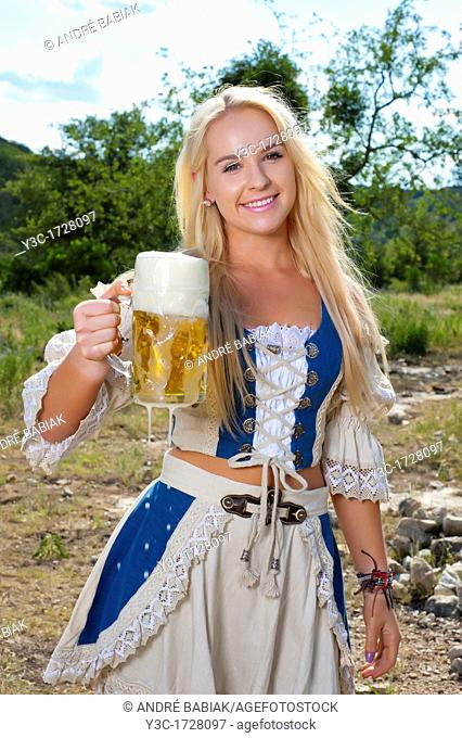 Blond German woman in traditional dirndl dress with beer glass