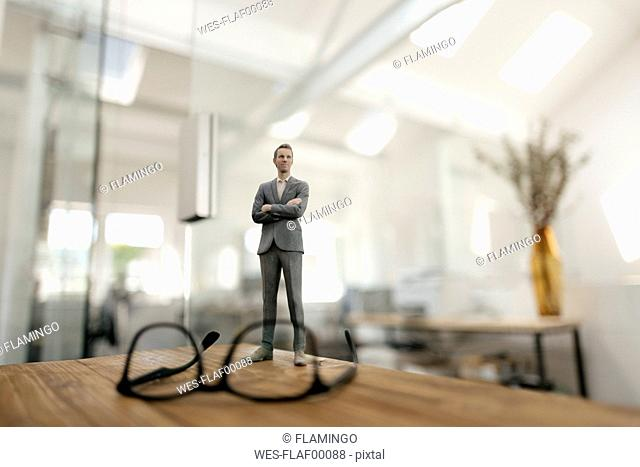 Businessman figurine standing behind glasses on desk in modern office