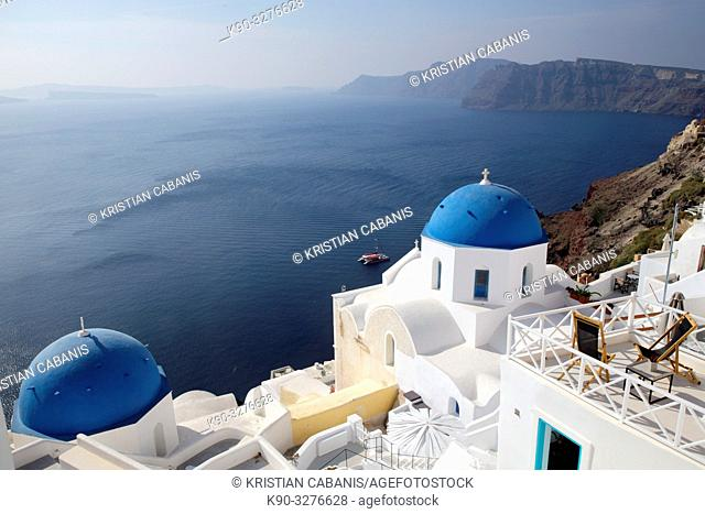 Church with blue roof top in Oia and overview of the caldera and neighboring islands, Santorin, Greece, Europe