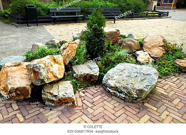 Decorative rock-garden in city street with benches in background as resting place