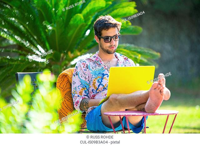 Man with feet up using laptop computer