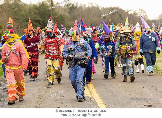 Cajun Mardi Gras revelers walk through the countryside going house to house during the Faquetigue Courir de Mardi Gras chicken run on Fat Tuesday February 17