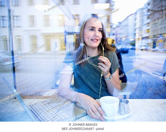 Young woman listening music in cafe