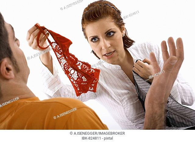 Woman reproachfully holding out a pair of panties to a man
