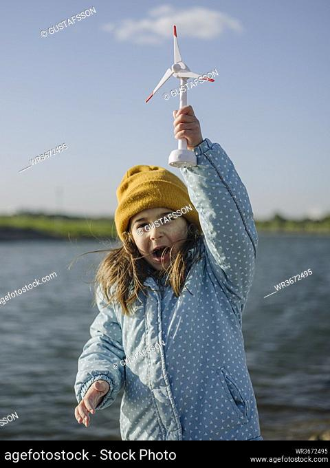Cheerful girl holding toy windmill screaming while standing against Rhine river during sunny day