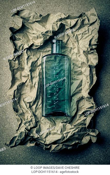 Blue glass bottle on a crumpled paper background