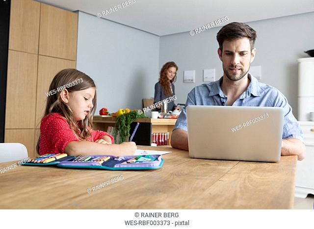 Man sitting at kitchen table using laptop while his little daughter painting