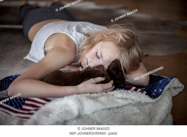 Teenage girl lying on floor and napping with puppy