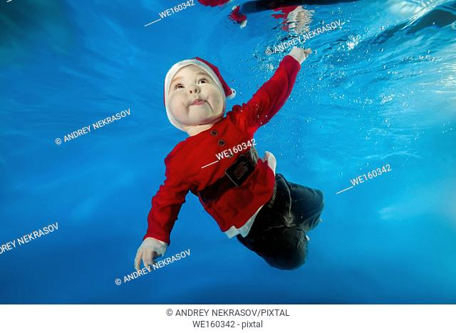 A little boy in Santa's cost swims underwater in the pool