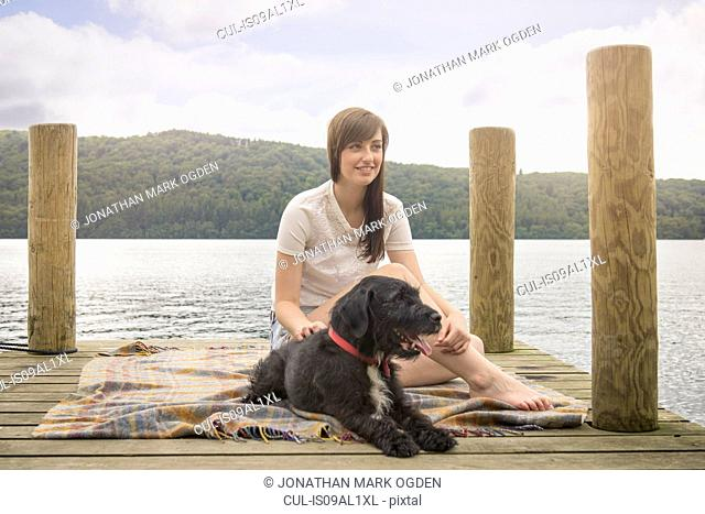 Young woman sitting with pet terrier at the end of a lakeside jetty