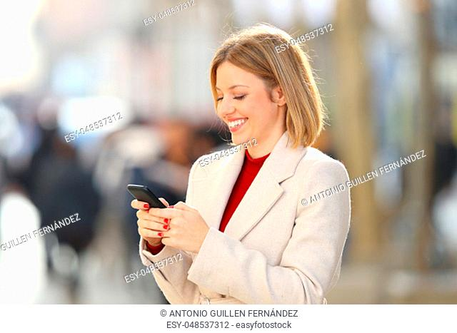 Happy woman using a smart phone in winter standing in the street