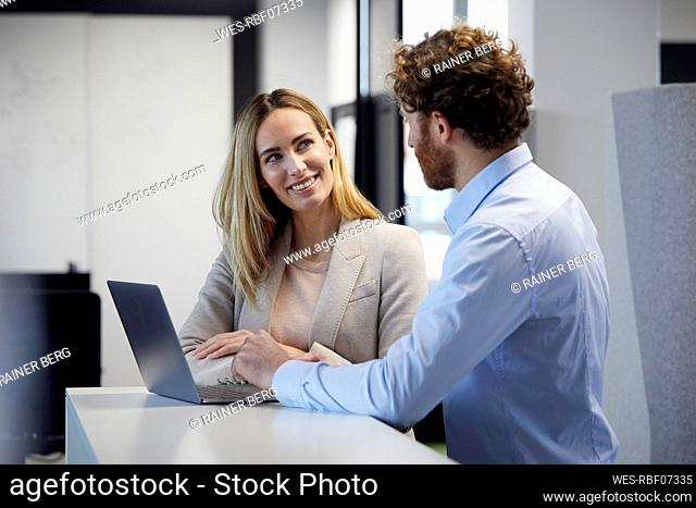 Businessman and businesswoman working together with laptop in office