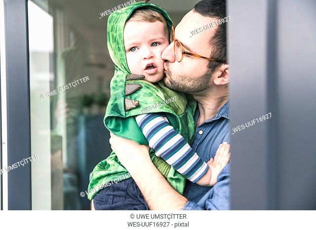 Father kissing son in a costume at terrace door at home