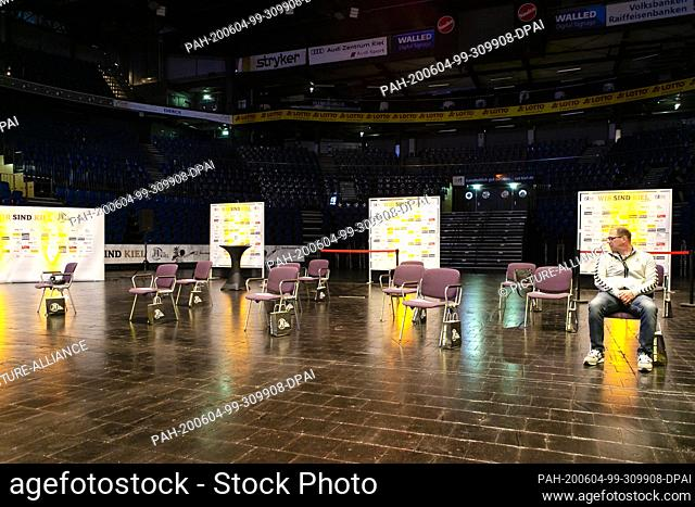 04 June 2020, Schleswig-Holstein, Kiel: Kiel's team coach Michael Menzel (r) sits alone in the Sparkassen-Arena in Kiel. Due to the Corona pandemic