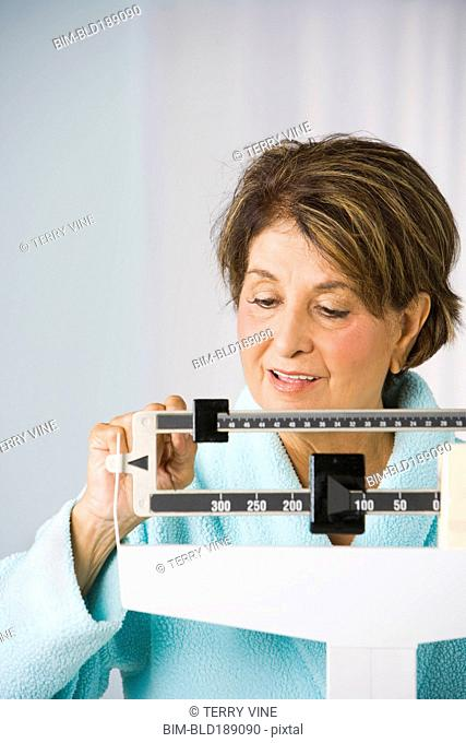 Senior Hispanic woman checking weight on scale