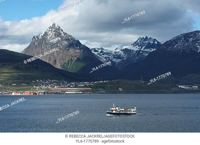 A pleasure boat sails in the Beagle Channel with a view of the city of Ushuaia and the mountains of Tierra del Fuego in the background. Argentina