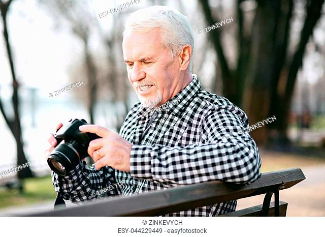 Creative person. Handsome mature man utilizing camera and looking down