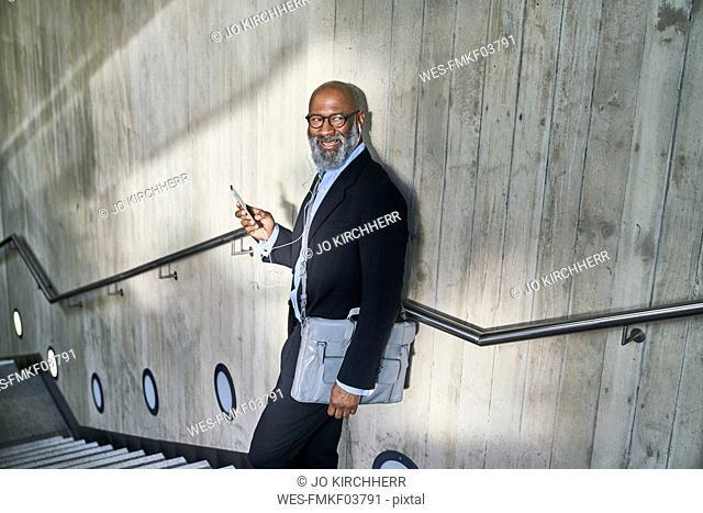 Businessman with crossbody bag using smartphone