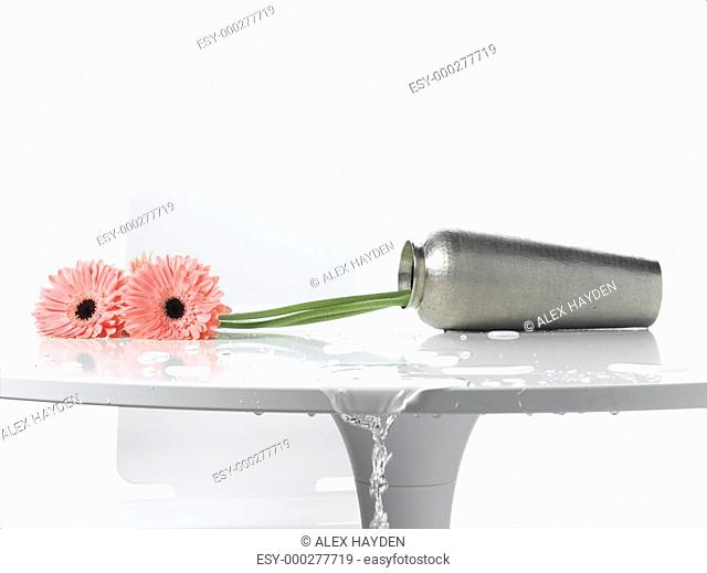 Water spilling out of vase on table