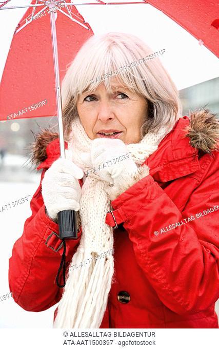 Elderly person with umbrella has cough