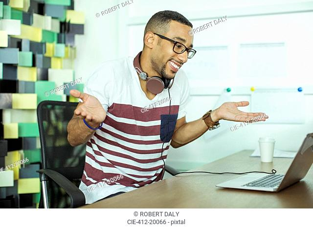 Man shrugging at laptop in office
