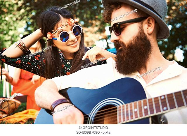 Young boho couple playing acoustic guitar at festival