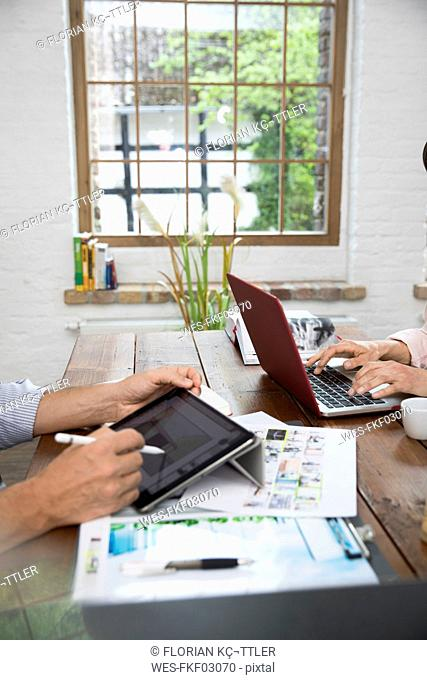 Mature couple working from their home office, using laptop and digital tablet