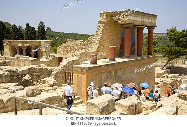 Tourists visiting the arcade of columns at the northern entrance of the palace on the grounds of the Minoan excavation of Knossos, Heraklion, island of Crete