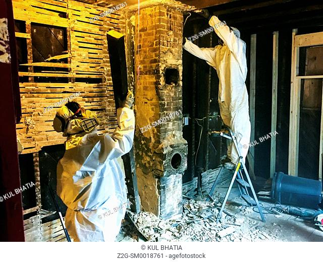 Two workers demolish the brickwork, plaster, and lath in a home renovation project, Halifax, Canada