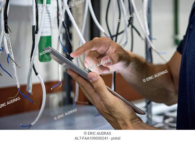 Electrician using digital tablet while inspecting equipment