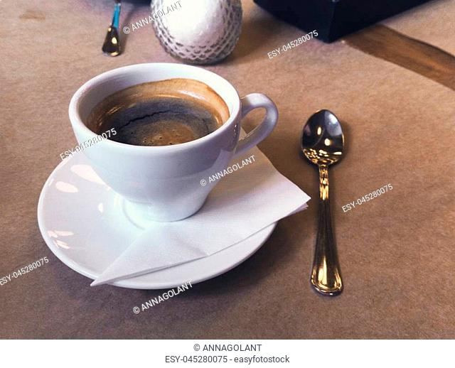 Breakfast in the cafe. Cup of Americano coffee in white mug, saucer and spoon. Close-up photo