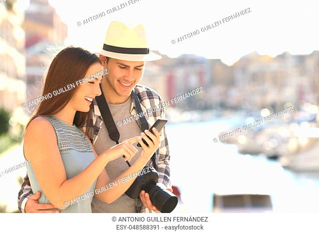 Couple of happy tourists booking hotel online with a smart phone on vacation in a coast town