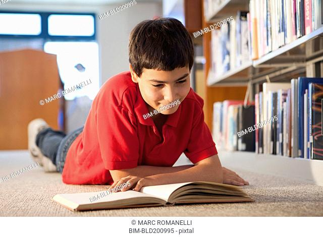 Hispanic boy reading book in library