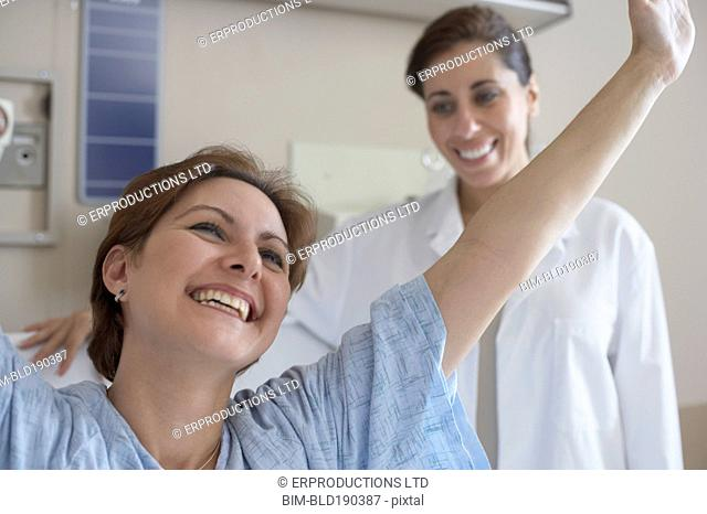 Hispanic woman in hospital gown with arms raised