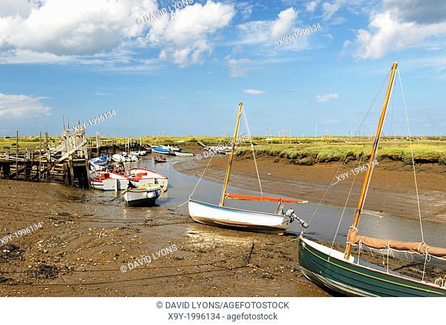 Fishing boats and landing quays on tidal Morston Creek in Blakeney National Nature Reserve, Norfolk, England