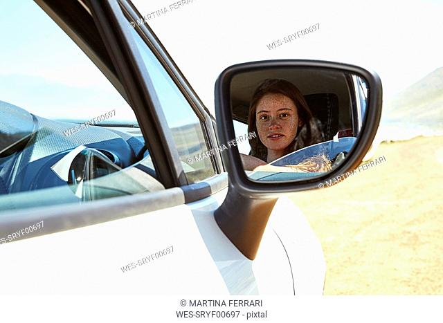 Reflection of young woman in wing mirror of a car