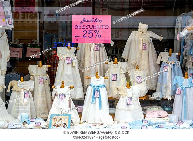 A store window filled with children's dresses in Seville , Spain
