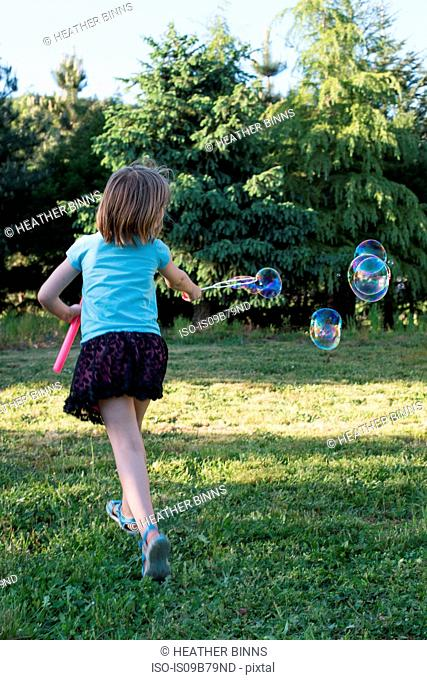 Young girl playing with bubble wand in garden, rear view