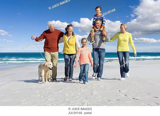 Multi-generation family with dog walking on sunny beach