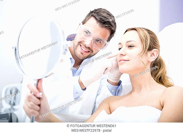 Aesthetic surgery, woman looking in mirror