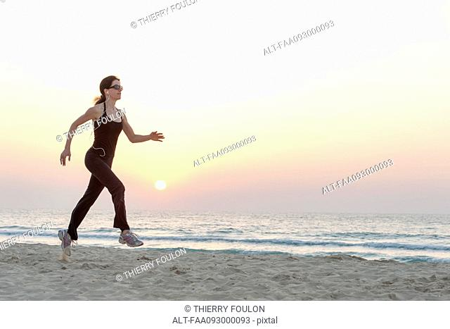 Woman with sunglasses jogging on beach at sunrise