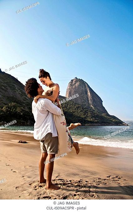 Couple hugging on beach, man lifting woman, Rio de Janeiro, Brazil