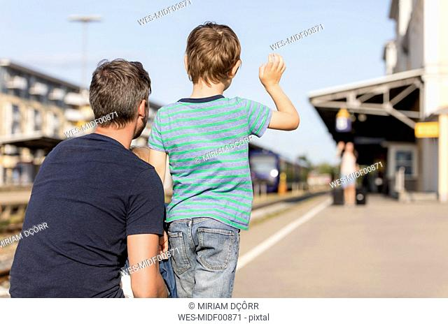 Son with father waving to mother on platform