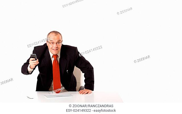 businessman sitting at desk and holding a mobilephone with copys pace