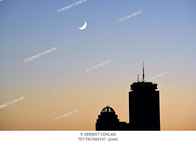 Crescent moon above office buildings