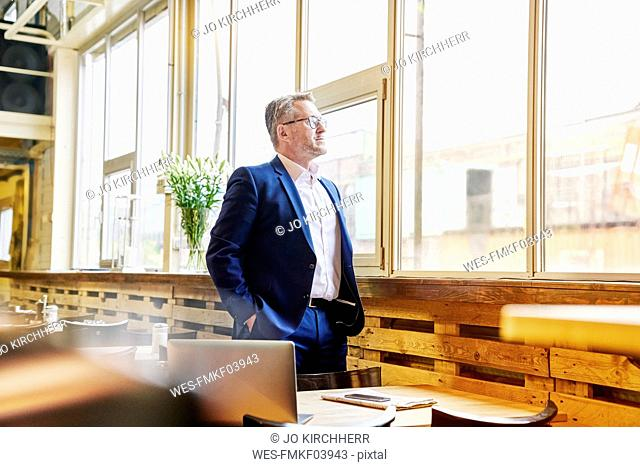 Mature businessman in cafe looking out of window