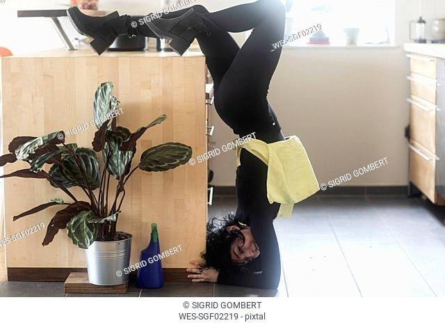 Young female dancer making handstand in the kitchen