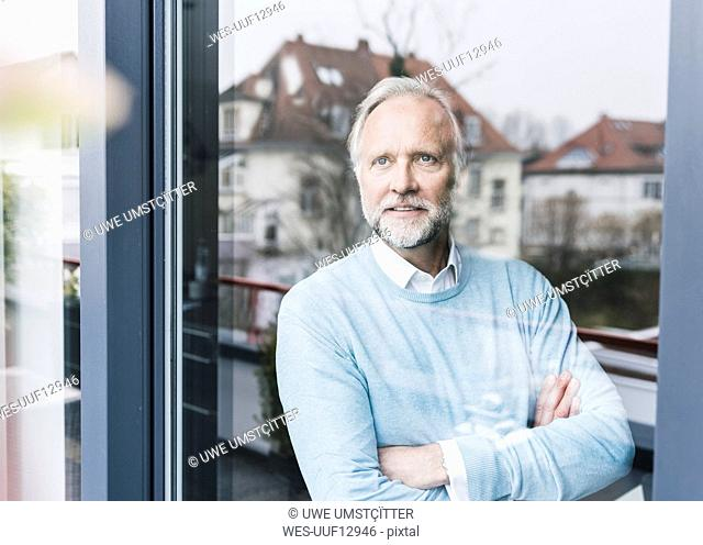 Portrait of mature man looking out of glass door