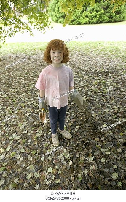 Young girl gardening in backyard